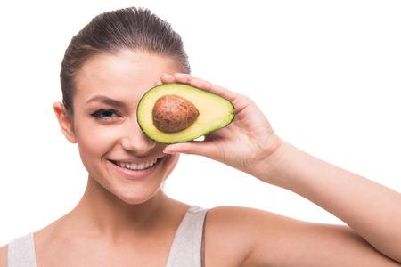 Jonge, lachende vrouw houdt avocado in de voorkant van haar oog op een witte achtergrond.