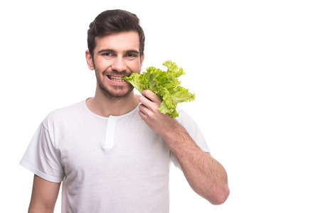 Portrait of handsome young man is chewing fresh lettuce leaves isolated on white background. photo