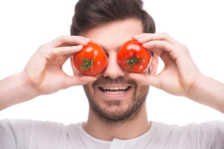 uomo rosso: Bel giovane � in possesso di pomodori davanti ai suoi occhi, mentre in piedi contro lo sfondo bianco.