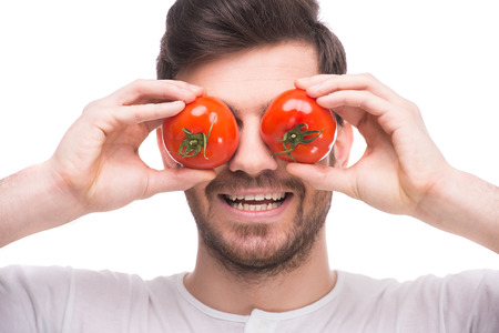eye red: Handsome young man is holding tomatoes in front of his eyes while standing against white background.