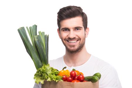 comiendo fruta: Hombre sonriente joven es la celebraci�n de las verduras, aislados en fondo blanco. Foto de archivo