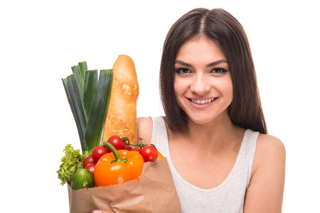 Young, smiling woman is holding a bag full of vegetables, on white background. photo
