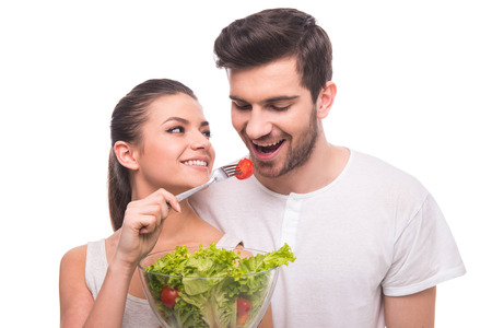 Healthy lifestyle. Beautiful couple are eating salad isolated on white background. Stock Photo