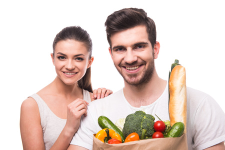 family shopping: Young, beautiful couple are holding a bag full of vegetables, on white background.
