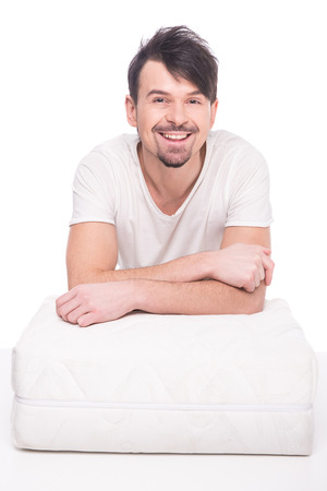 sleep well: Young man is showing nice mattress that supported you to sleep well all night.