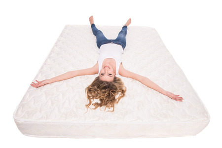 Young, smiling woman is lying on the quality mattress over white background. Reklamní fotografie