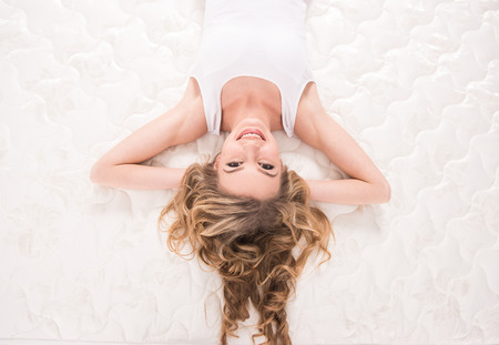 Young, smiling woman is lying on the quality mattress over white background. Stock Photo