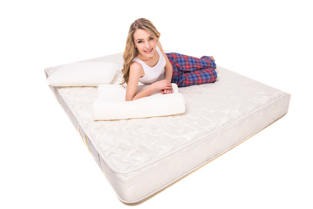 camra: Young, smiling woman is lying on the quality mattress and looking at the camra, over white background. Stock Photo