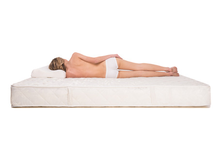 Back view of young woman is lying on quality mattress.