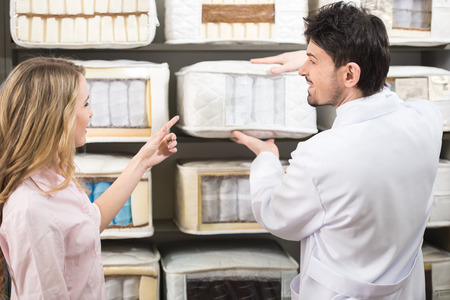 The young salesman tells the customer about quality mattresses in the store. Stock Photo