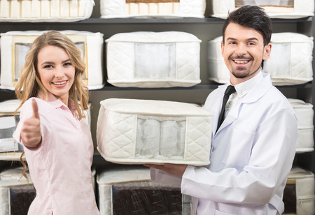 salesman: The young salesman tells the customer about quality mattresses in the store. Stock Photo