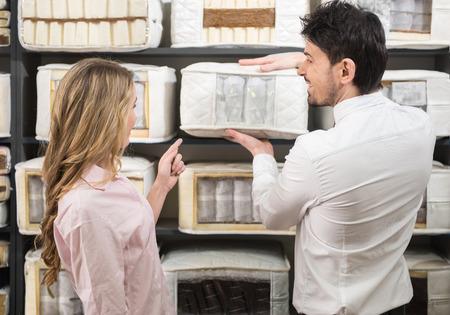 De jonge verkoper vertelt de klant over de kwaliteit matrassen in de winkel.