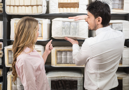 The young salesman tells the customer about quality mattresses in the store. Foto de archivo