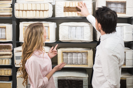 The young salesman tells the customer about quality mattresses in the store. Фото со стока