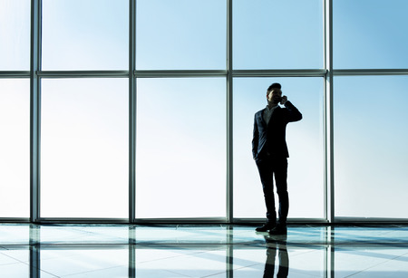panoramic windows: Silhouette view of young businessman is standing in modern office with panoramic windows.