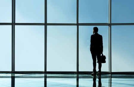 windows: Silhouette view of young businessman is standing in modern office with panoramic windows.