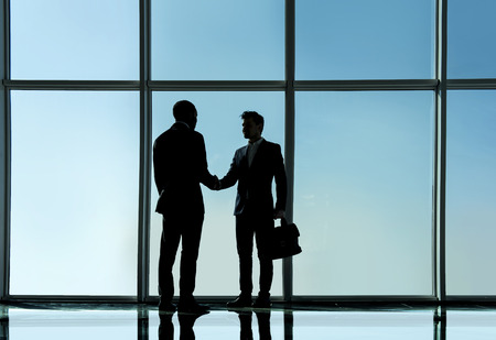 panoramic windows: Silhouette view of two young businessmen are standing in modern office with panoramic windows. Stock Photo