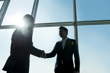 business meeting: View from below of two young businessmen are standing in modern office with panoramic windows.