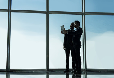 panoramic windows: Silhouette view of two young businessmen are making selfie photo in modern office with panoramic windows.