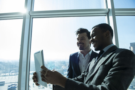 panoramic windows: View of two young businessmen are making selfie photo in modern office with panoramic windows. Stock Photo