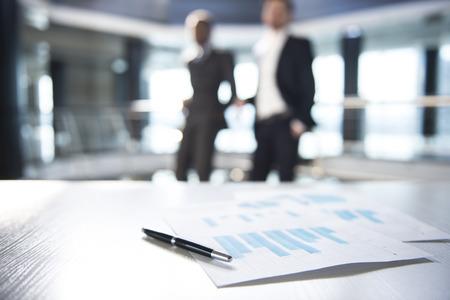 reunion de trabajo: Centrarse en los documentos y lápiz sobre la mesa. Gente enmascarada en el fondo.