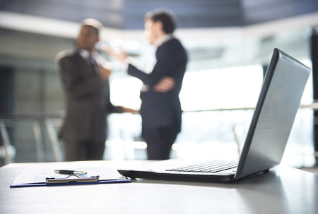 dos personas platicando: Centrarse en la computadora port�til sobre la mesa. Gente enmascarada en el fondo.