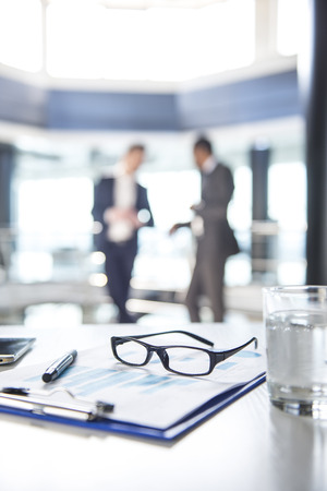 modern business: Focus on the things on the table. Blurred people on background.