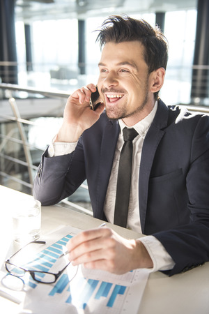 Young businessman is sitting at the table, talking by phone and smiling. photo