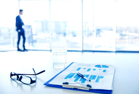 financial services: Focus on the things on the table. Blurred man near panoramic windows on background.