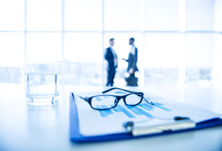 law office: Focus on the things on the table. Blurred men near panoramic windows on background. Stock Photo
