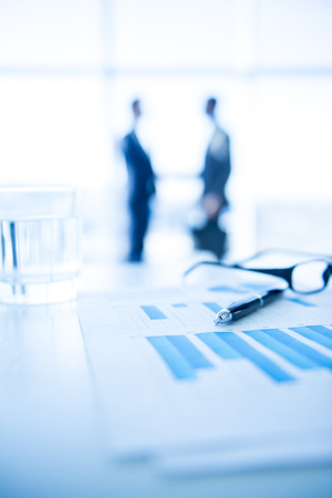 panoramic windows: Focus on the things on the table. Blurred men near panoramic windows on background. Stock Photo