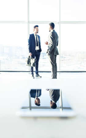Two young businessmen in the modern office near panoramic windows are talking. Their images in the phone that is on the table.