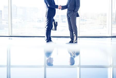 Dos jóvenes empresarios están temblando las manos unos con otros de pie en una habitación con ventanas panorámicas.