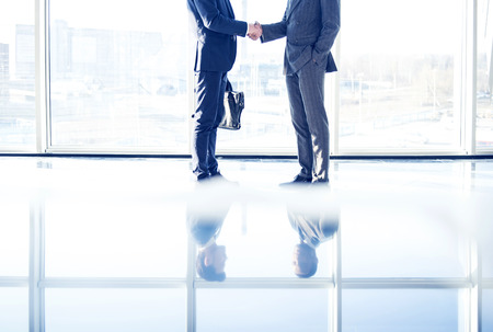 Two young businessmen are shaking hands with each other standing in a room with panoramic windows.