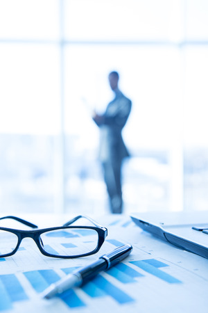 Focus on the things on the table. Blurred man near panoramic windows on background.