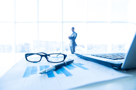 corporate consulting: Focus on the things on the table. Blurred man near panoramic windows on background.