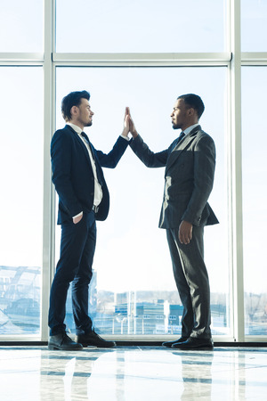 panoramic windows: Two young businessmen are shaking hands with each other standing in a room with panoramic windows.
