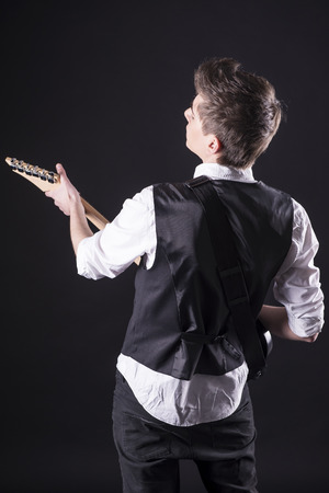 Back view of young guitarist with the electric guitar, isolated on dark background. photo