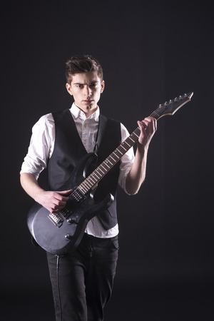 Young guitarist with the electric guitar, isolated on dark background is looking at the camera. photo