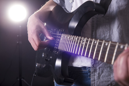 Guitar player. Close-up hands of young man is playing guitar in dark room with lights behind him. photo
