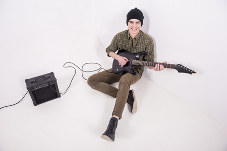 Young male musician is playing a six-string bass guitar in studio with amp. photo