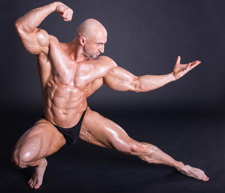 hombres sin camisa: Bodybuilder est� planteando, que muestra sus m�sculos. Fuerza, alivio, los m�sculos, el coraje, la virilidad, culturista, culturismo. Foto de archivo
