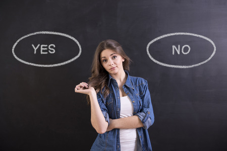 Young woman is standing on blackboard background and thinking: yes or no.