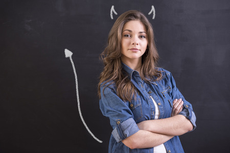 imp: Young woman is standing in front of blackboard like imp.