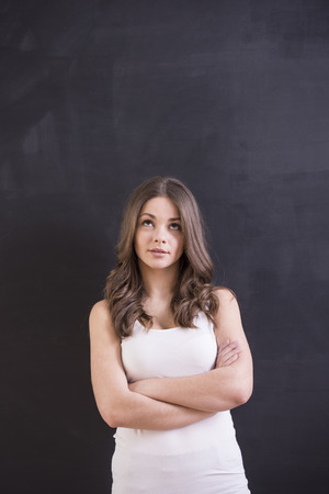 Thinking young woman is standing on blackboard background. photo