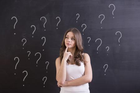 preguntando: Mujer joven con la expresión y signos de interrogación dudosos en la pizarra detrás de ella.
