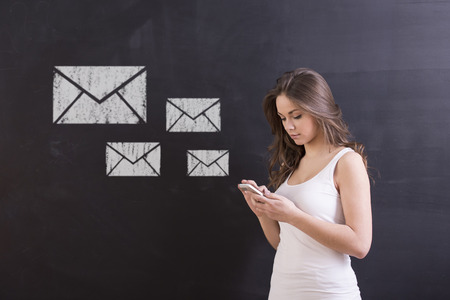 email lists: Social network concept. Young woman is standing in front of blackboard and typing a message.