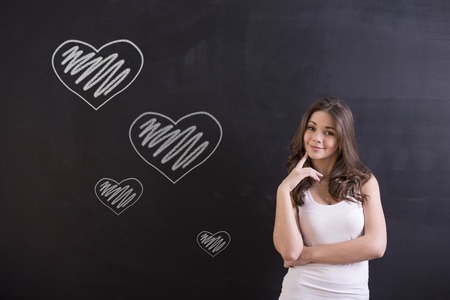 Portrait of pretty girl in front of blackboard is thinking of falling in love. Stock Photo
