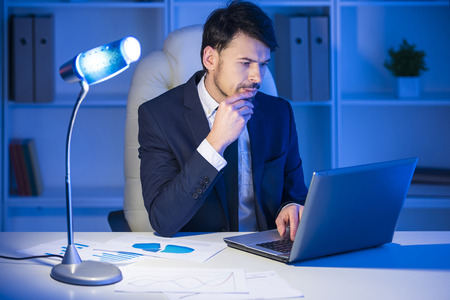 Confident man is working on laptop in office. photo