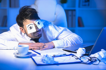 A tired businessman with adhesive note on his eyes. Concept of sleeping.
